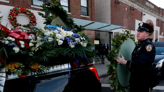 An NYPD officer loads flowers onto a vehicle outside Officer Ramos' funeral.