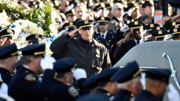 Police officers salute as the casket of Officer Rafael Ramos arrives before the funeral.