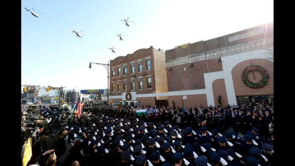 Law enforcement helicopters fly over Christ Tabernacle in Queens, where the casket of New York City police officer Rafael Ramos is carried by pallbearers, on Saturday, December 27. Ramos and Officer Wenjian Liu were shot and killed while they sat in their patrol car in Brooklyn on December 20.