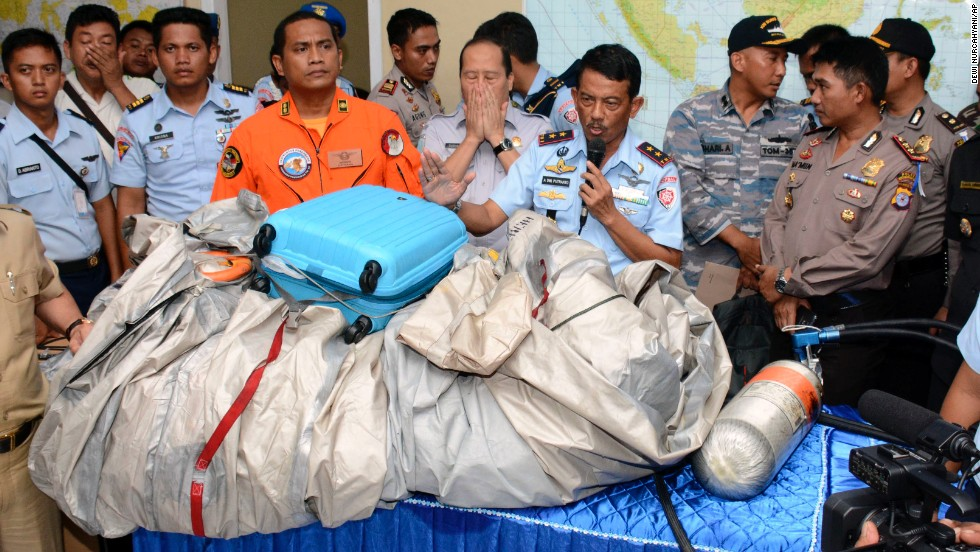 Indonesian air force personnel show debris, including a suitcase, that was found floating near the site where the AirAsia flight disappeared.