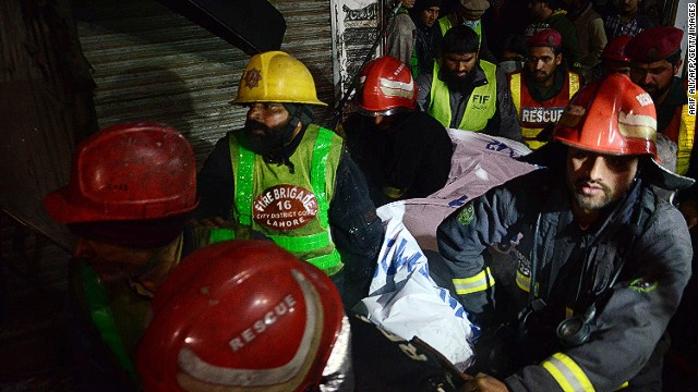 Volunteers move a victim after a fire in a four-storey building in Lahore, Pakistan on December 29, 2014.