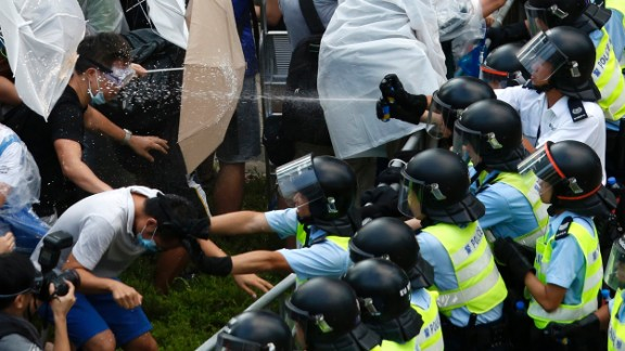 "Riot police use pepper spray as they clash with pro-democracy protesters outside the government headquarters in Hong Kong on September 28, 2014. Demonstrations began in response to China's decision to allow only Beijing-vetted candidates to stand in the city's 2017 election for chief executive. Protesters say Beijing has gone back on its pledge to allow universal suffrage in Hong Kong, which was promised ""a high degree of autonomy"" when it was handed back to China by Britain in 1997. The umbrella has become the defining image of the protest movement, used to shield protesters from tear gas and the elements."