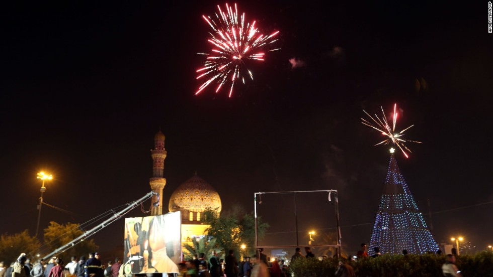 Iraqi crowds cheer as fireworks begin at Firdos Square in Baghdad.