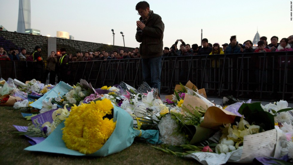 A man prays after laying flowers at the site of a deadly stampede in Shanghai, China, on Thursday, January 1. The city government said 36 people died and 47 were injured in the incident, which occurred during New Year's Eve festivities, less than a half-hour before midnight. Many of the victims were female students, state media reported.