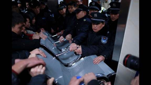 Security guards use a bench to hold off relatives of victims trying to enter the emergency area of a hospital in Shanghai. One woman told state broadcaster CCTV that relatives had been waiting for hours for information about their loved ones.