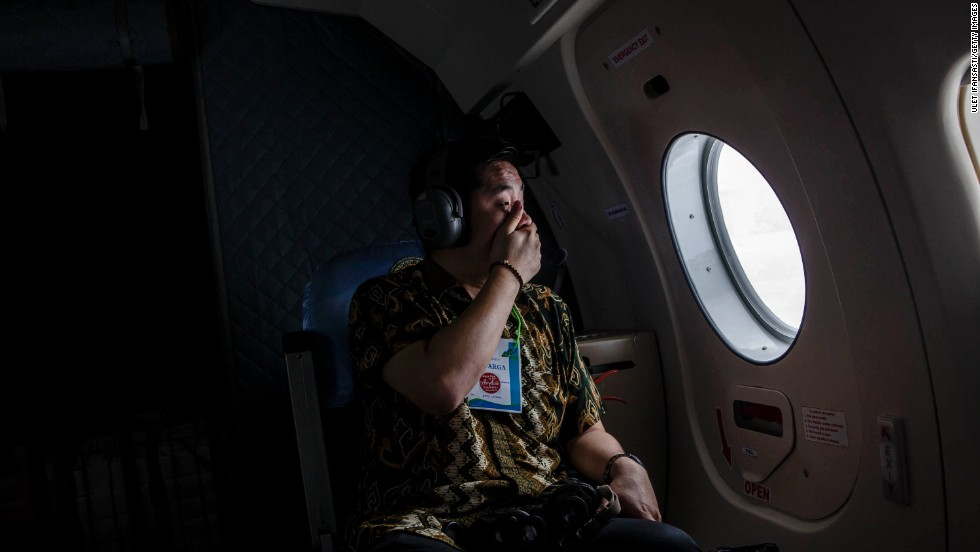 "A relative of a missing passenger looks out over the Java Sea during <a href=""http://www.cnn.com/2014/12/28/asia/gallery/airasia-missing-plane/index.html"" target=""_blank"">the search for AirAsia Flight QZ8501</a> on Tuesday, December 30. Search teams <a href=""http://www.cnn.com/2015/01/01/world/asia/airasia-disaster/index.html"" target=""_blank"">found debris and some bodies in the water</a> two days after the plane took off from Surabaya, Indonesia. It was carrying 155 passengers and seven crew members."