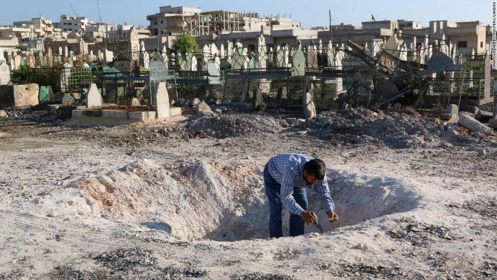 A man in Khan Sheikhoun, Syria, inspects a hole in the ground after what activists said was an airstrike carried out by forces loyal to Syrian President Bashar al-Assad on Friday, December 26.