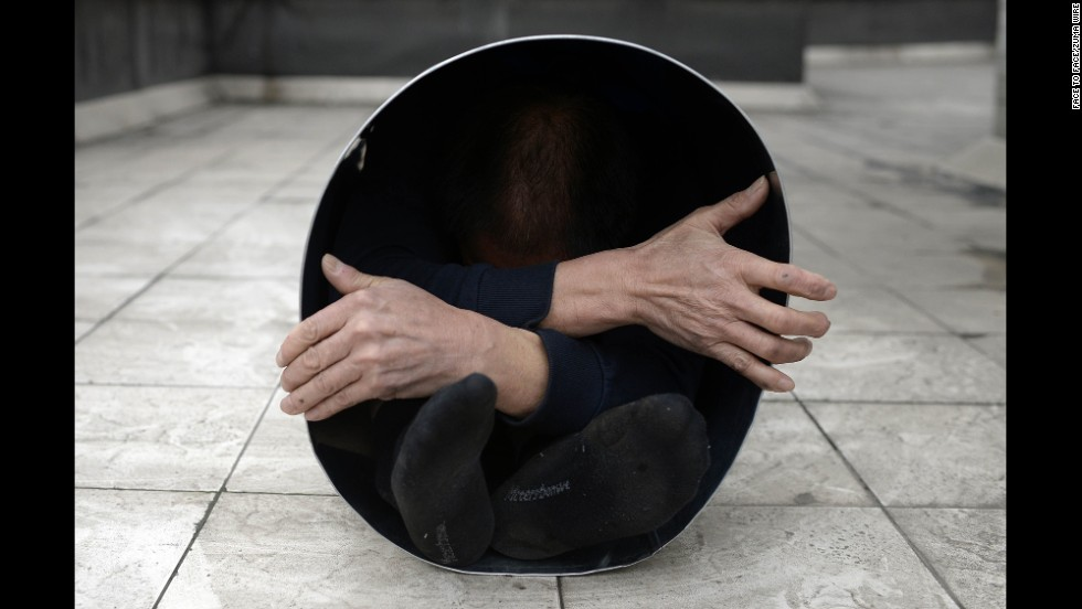 A man folds himself into a metal bucket in Chongqing, China, on Friday, December 26.