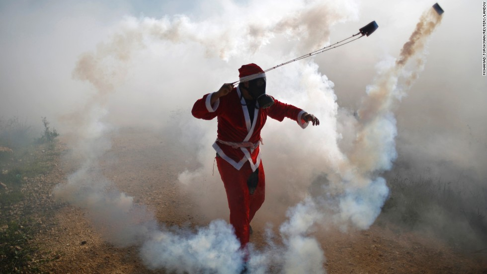 A Palestinian protester, dressed as Santa Claus, uses a slingshot to return a tear gas canister fired by Israeli troops during clashes in the West Bank village of Bilin on Friday, December 26.