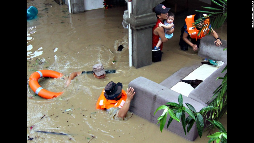 Police officers in Mindanao, Philippines, help families who were trapped in their homes during heavy flooding on Monday, December 29. The flooding was brought on by Tropical Storm Seniang.