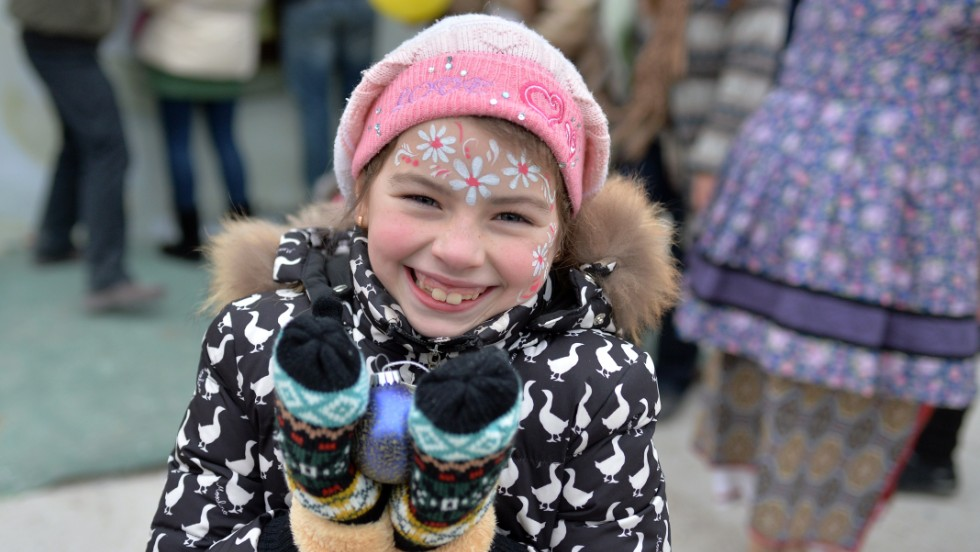 DECEMBER 29 -- UKRAINE, KIEV:  A young girl smiles while holding an ornament during a New Years celebration at an assistance center. Thousands of families displaced by fighting in eastern Ukraine are receiving humanitarian assistance at a center set up by volunteers in Kiev.