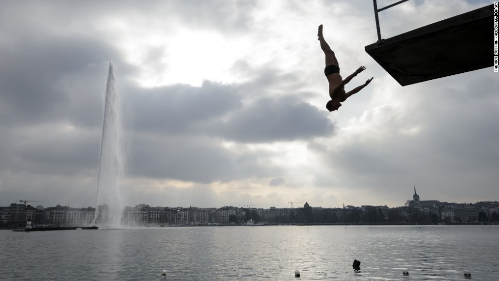 "JANUARY 1 -- GENEVA, SWITZERLAND: A man dives from a platform into Lake Geneva during a New Years Day swim. Around 50 swimmers took part in the traditional dip, now in its 21st year. Similar ""ice swims"" were held in cities across Europe."