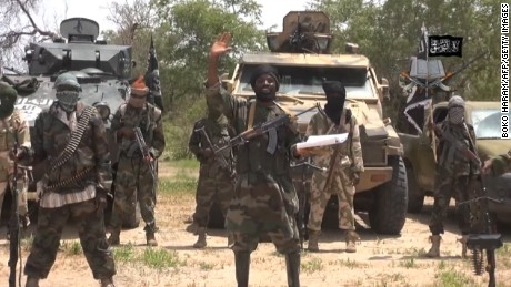"FILES) -- A screengrab taken on July 13, 2014, from a video released by the Nigerian Islamist extremist group Boko Haram and obtained by AFP shows the leader of the Nigerian Islamist extremist group Boko Haram, Abubakar Shekau (C). Boko Haram gunmen killed 48 fish vendors in Nigeria's restive Borno State, near the border with Chad, the head of the fish traders association told AFP on November 25, 2014. ""Scores of Boko Haram fighters blocked a route linking Nigeria with Chad near the fishing village of Doron Baga on the shores of Lake Chad on Thursday and killed a group of 48 fish traders on their way to Chad to buy fish, "" Abubakar Gamandi said. AFP PHOTO / BOKO HARAM"