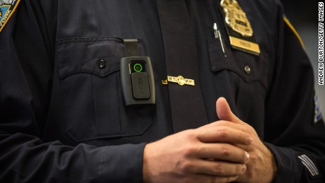 NYPD Sgt. Joseph Freer demonstrates how to use a body camera during a press conference.