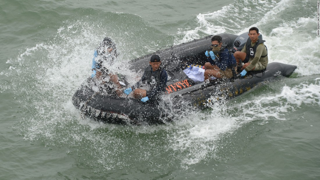Members of the Indonesian navy return to the vessel with remains recovered from the crash area.