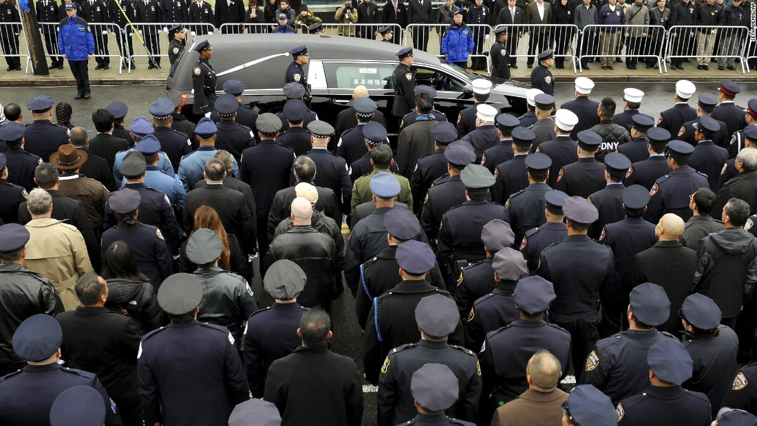 A hearse carrying the body of Officer Wenjian Liu passes by police officers in formation after his funeral in Brooklyn, New York, on Sunday, January 4.