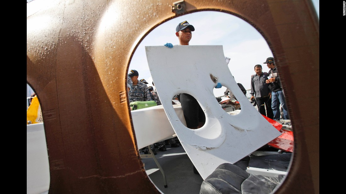 An Indonesian navy member holds a piece of window panel that was recovered during search operations.