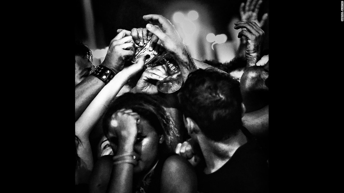 People reach for a bottle at an Avenged Sevenfold performance in 2013.