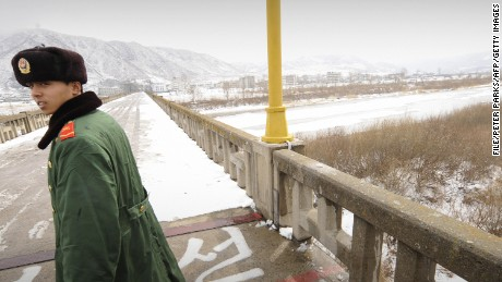This file photo from 2009 shows a Chinese border guard patrolling on a bridge over the Tumen River that marks the border between China and North Korea.