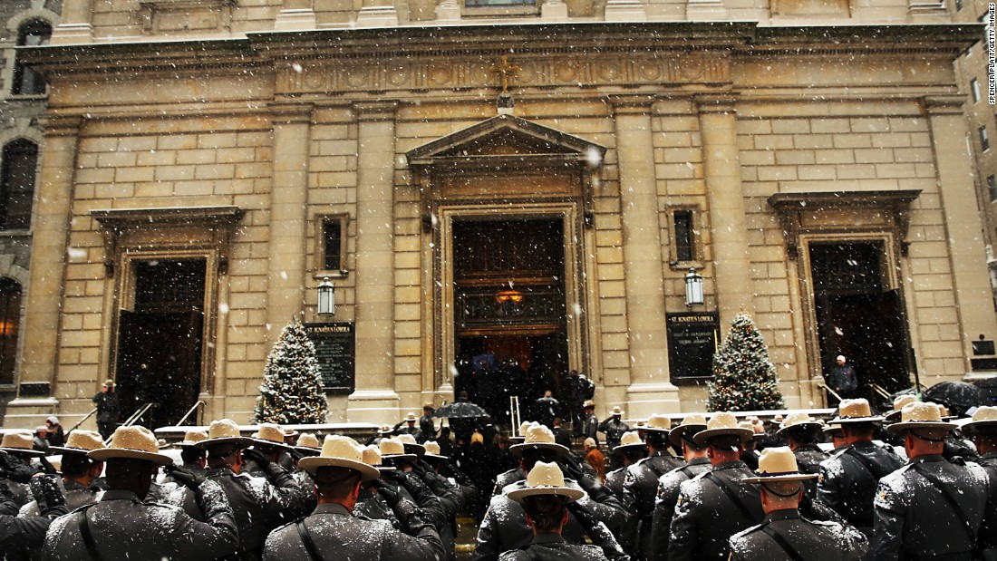 New York State Police wait for the hearse carrying Cuomo's casket.