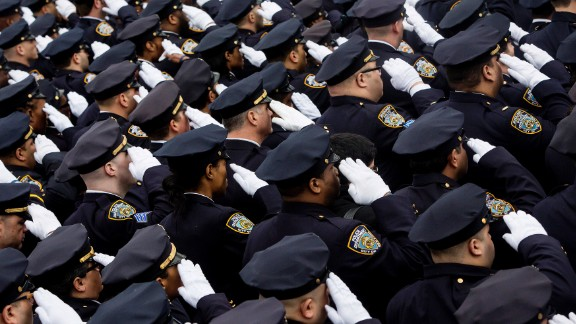 New York City Police Officers salute following the funeral service for New York City Police Officer Wenjian Liu during his funeral service at Aievoli Funeral Home in the Dyker Heights neighborhood on January 4, 2015 in the Brooklyn borough of New York City.
