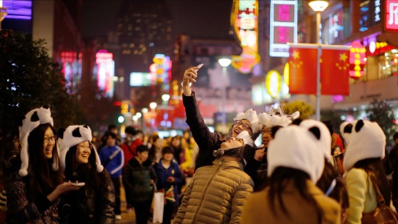 Tourists wearing panda hats take a selfie during a New Year's celebration in Shanghai, China, on Thursday, January 1.
