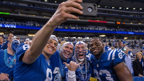 Indianapolis Colts quarterback Matt Hasselbeck snaps a photo with teammate Dwayne Allen, right, and two fans after the Colts defeated Cincinnati in a playoff game Sunday, January 4, in Indianapolis.