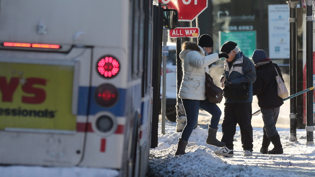 Bus riders step across a snow-piled sidewalk on January 6 in Chicago.