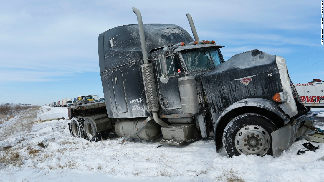 A truck remains on the side following a crash involving several vehicles on January 6, a few miles south of Remington, Indiana. The highway's southbound lanes were iced over following a winter storm that swept across Indiana overnight.