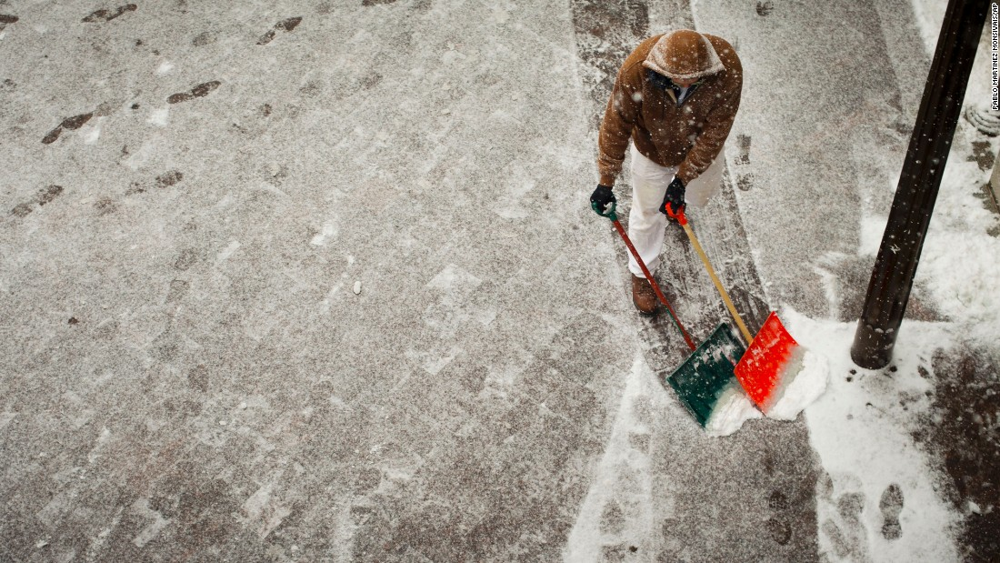 A worker helps clear the sidewalk entrance to the U.S. Capitol in Washington on January 6.