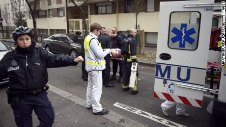 Firefighters carry an injured man on a stretcher in front of the offices of the French satirical newspaper Charlie Hebdo in Paris on January 7, 2015, after armed gunmen stormed the offices leaving at least 10 people dead. AFP PHOTO / MARTIN BUREAU        (Photo credit should read MARTIN BUREAU/AFP/Getty Images)