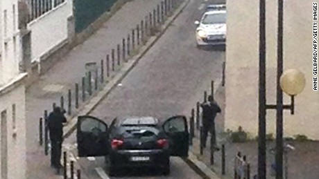 Armed gunmen face police officers near the offices of the French satirical newspaper Charlie Hebdo in Paris on January 7, 2015, during an attack on the offices of the newspaper which left eleven dead, including two police officers, according to sources close to the investigation. AFP PHOTO / ANNE GELBARDANNE GELBARD/AFP/Getty Images