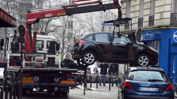 A tow truck lifts the car used by the gunmen.