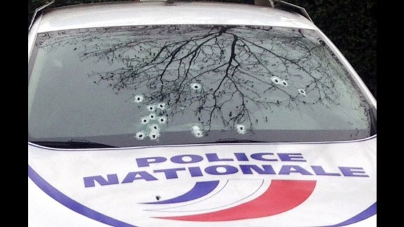 A police car sits riddled with bullets.