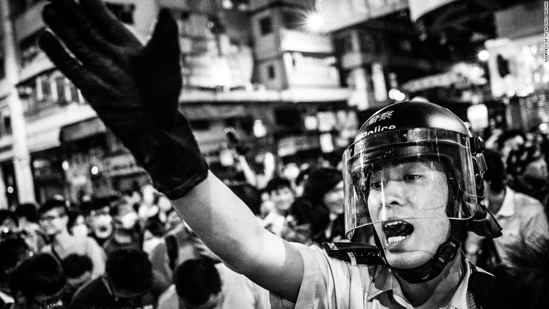 A policeman attempts to get protesters off the streets in Mong Kong, a gritty, working-class neighborhood.