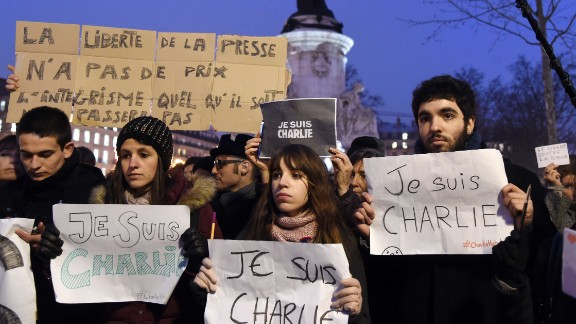 People hold signs during a gathering in Paris on January 7.