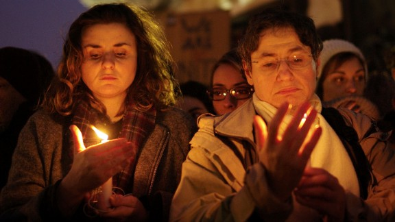 People in Paris hold candles on January 7.