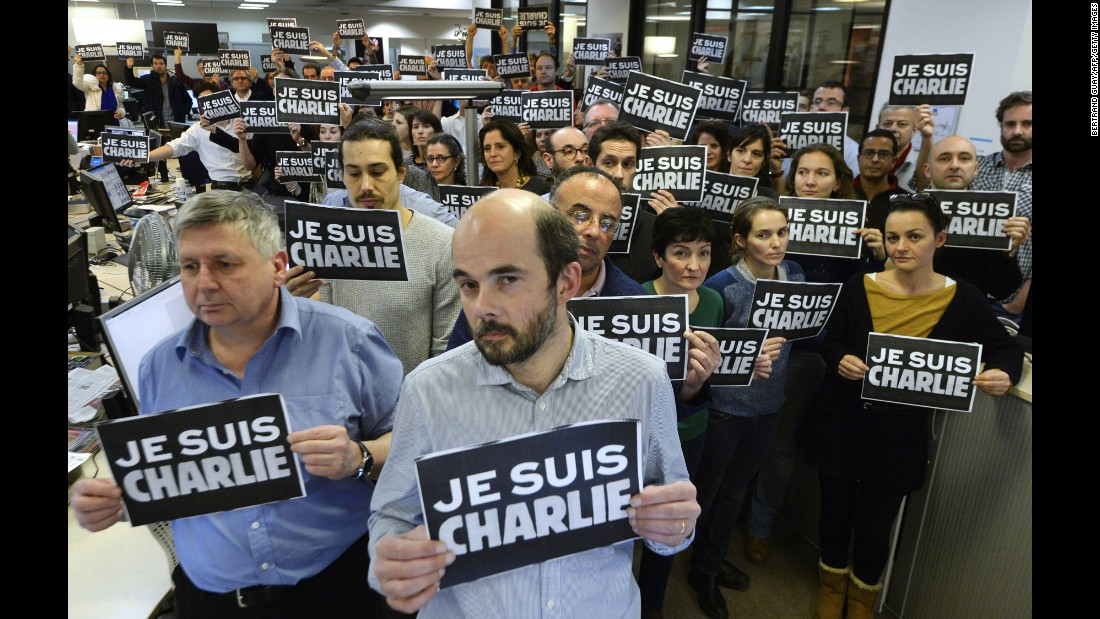 "Journalists with Agence France-Presse hold signs reading ""I am Charlie"" as they observe a minute of silence on January 7."