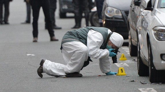 Police officers inspect evidence at the scene of the shooting.