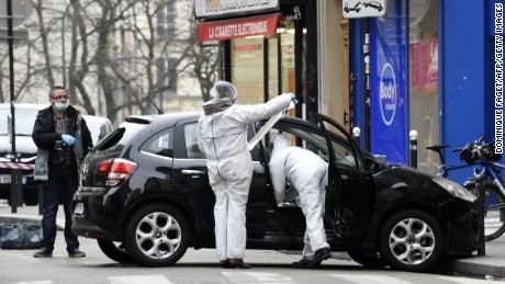 French police officers and forensic experts examine the car used by armed gunmen who stormed the Paris offices of satirical newspaper Charlie Hebdo, killing 12 people, on January 7, 2015 in Paris.