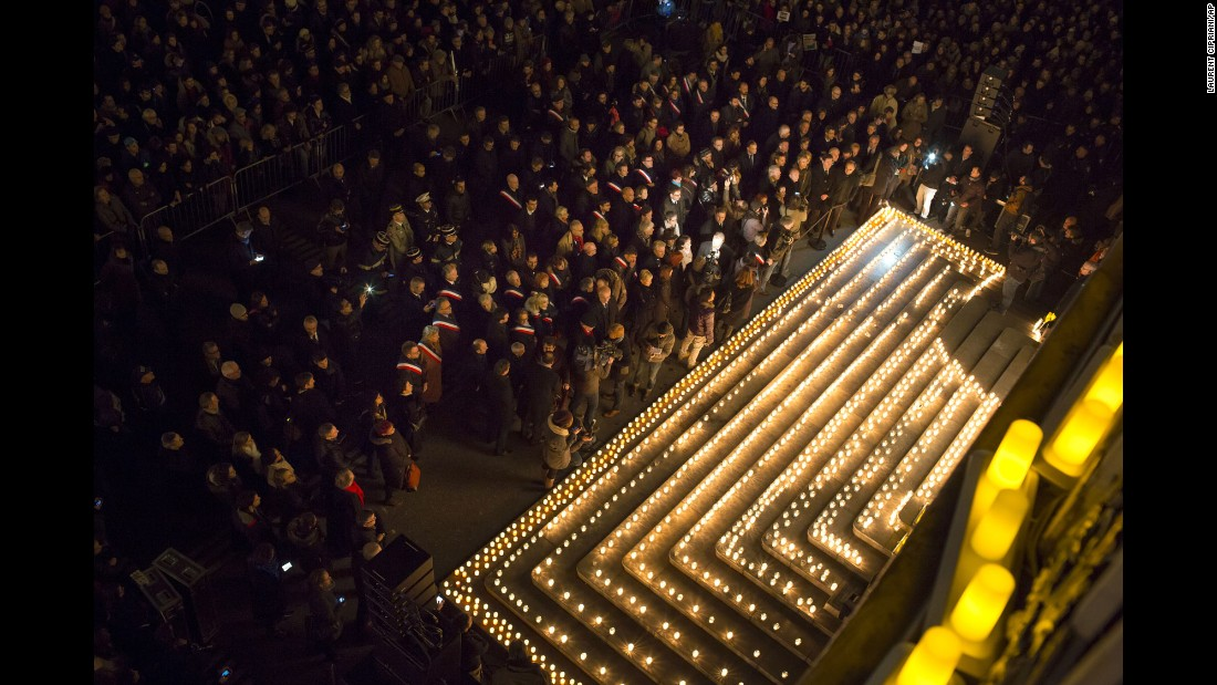 People gather near candles in Lyon, France, on January 7.