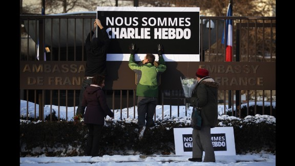 Employees put up a sign as a woman prepares to place a bouquet of flowers at the front gate of the French Embassy in Washington on January 7.