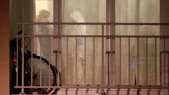 Forensics officers are seen through a window in Reims.