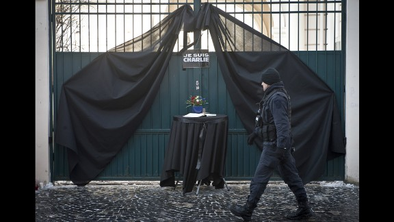 A Romanian military member walks past a condolence book outside the French Embassy in Bucharest, Romania, on January 8.