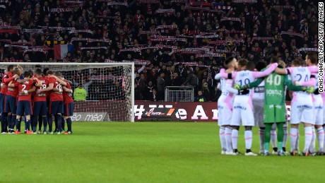 Evian's and Lille's players observe a minute's silence for the victims of the attack on a French satirical magazine.