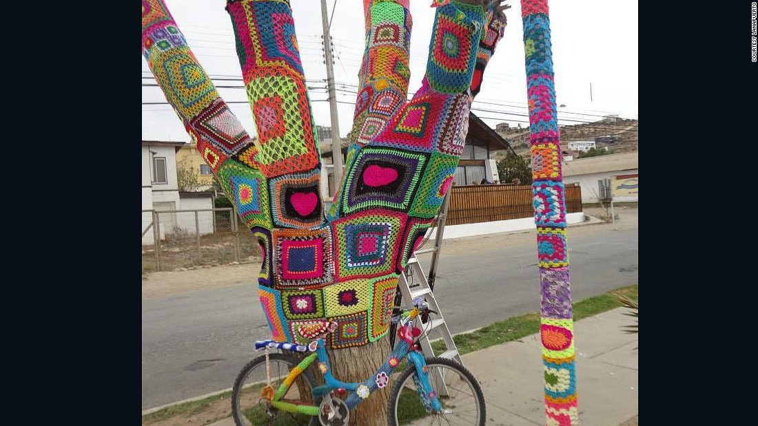 A large tree, bicycle and lamp post display colorful yarn-bombing creations made by Lanapuerto.