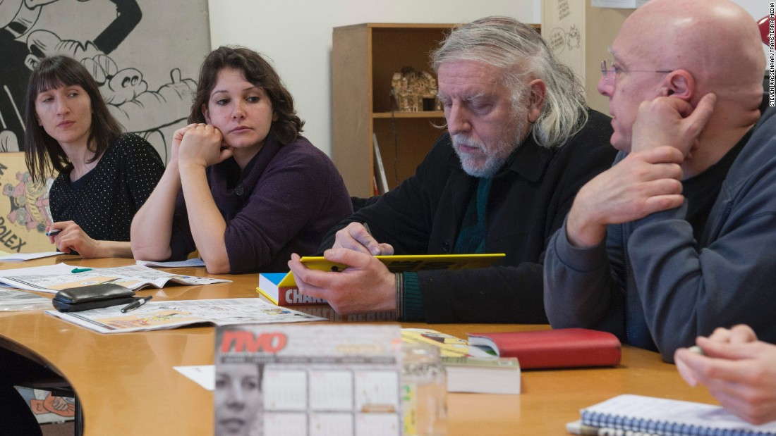 Cartoonist Philippe Honore, second from right, meets with other staff members in 2012. Honore, who illustrated a cartoon featured on Charlie Hebdo's Twitter feed Wednesday morning, was among those killed in the attack. The cartoon is a drawing of ISIS leader Abu Bakr al-Baghdadi offering his best wishes for 2015.