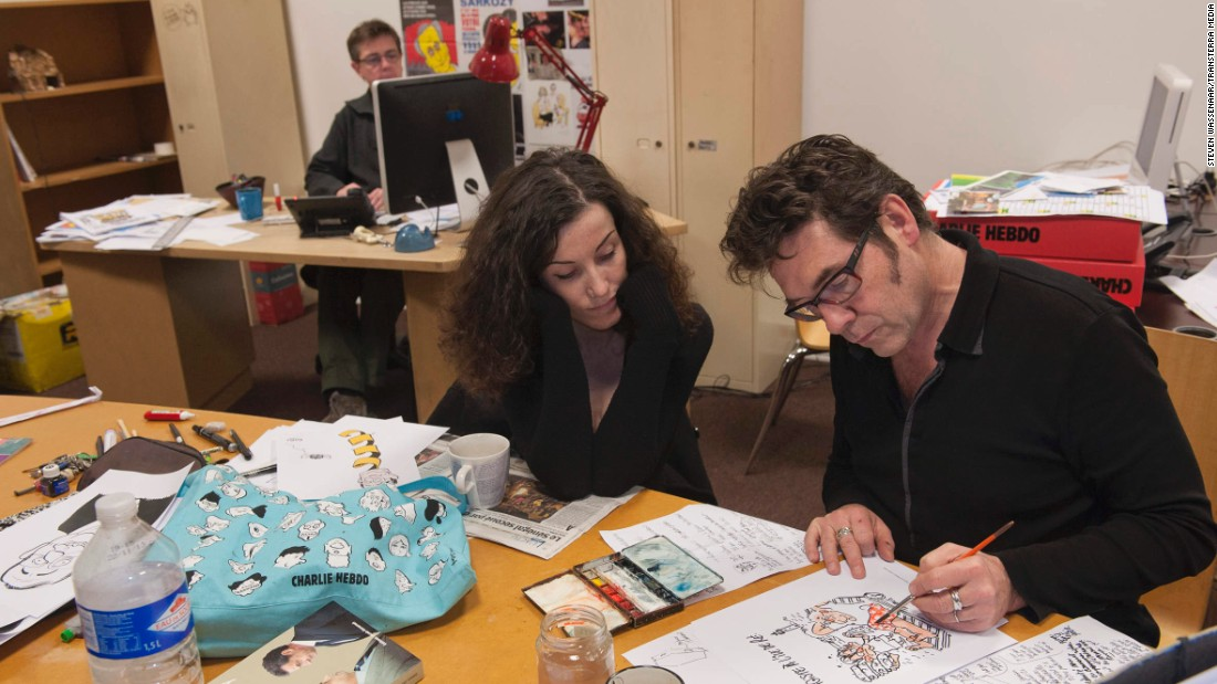 "Verlhac sketches a political cartoon with Corinne Rey, a cartoonist also known as Coco, in 2012. Charbonnier is in the background. Rey said she took refuge under a desk <a href=""http://www.cnn.com/2015/01/08/europe/charlie-hebdo-attack-timeline/"" target=""_blank"">as her colleagues were killed.</a>"