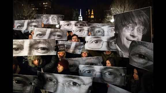 Mourners hold signs depicting victims' eyes during a rally in New York on Wednesday, January 7.