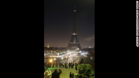 The Eiffel tower's lights are switched off in Paris on January 8, 2015, in tribute to the twelve people killed the day before in an attack by two armed gunmen on the offices of French satirical newspaper Charlie Hebdo in Paris. A huge manhunt for two brothers suspected of massacring 12 people in an Islamist attack at a satirical French weekly zeroed in on a northern town after the discovery of one of the getaway cars. As thousands of police tightened their net, the country marked a rare national day of mourning for Wednesday's bloodbath at Charlie Hebdo magazine in Paris, the worst terrorist attack in France for half a century. AFP PHOTO / JACQUES DEMARTHON (Photo credit should read JACQUES DEMARTHON/AFP/Getty Images)